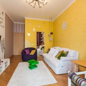 Белые диван около желтой стены