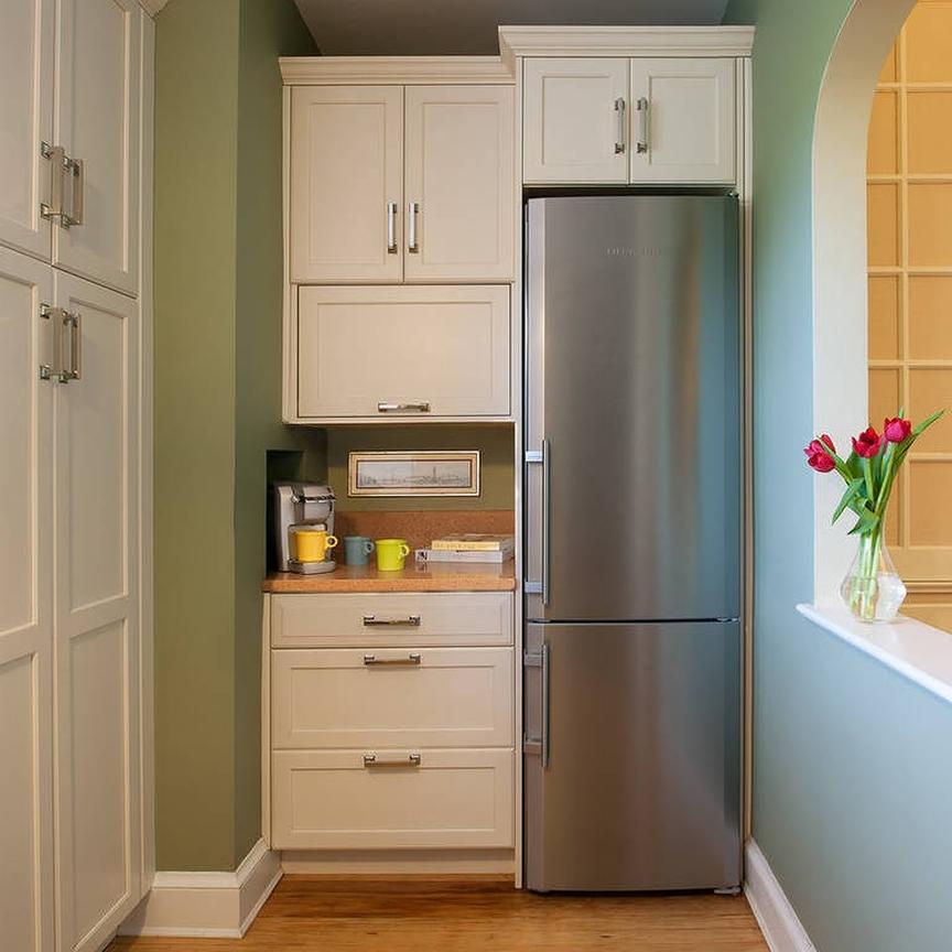 Кофеварка на тумбе возле холодильника