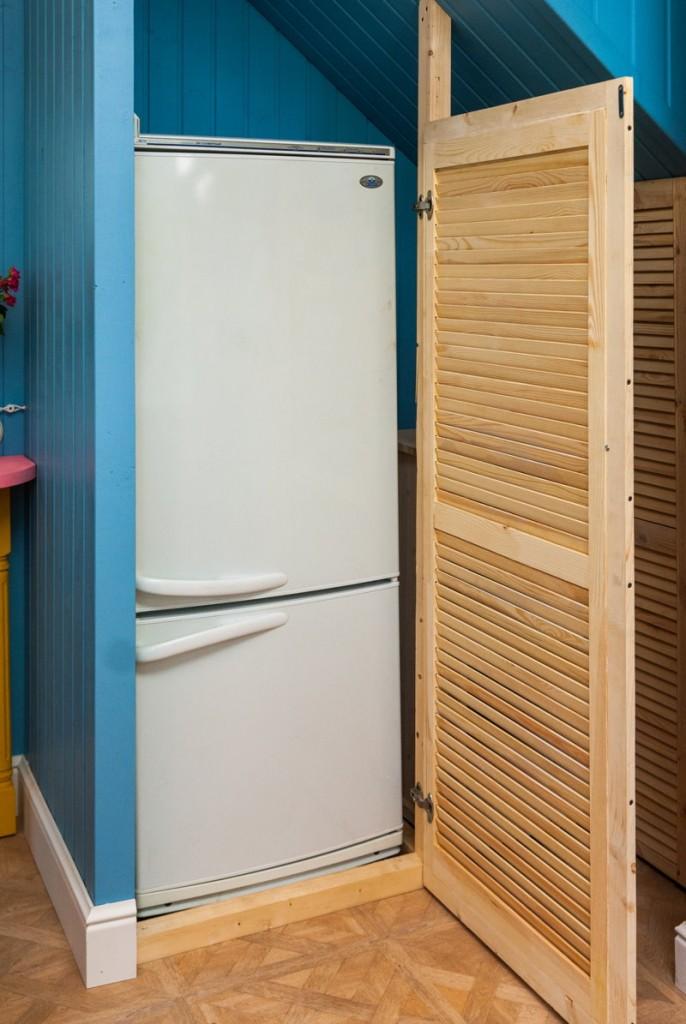 Белый холодильник в кладовке частного дома