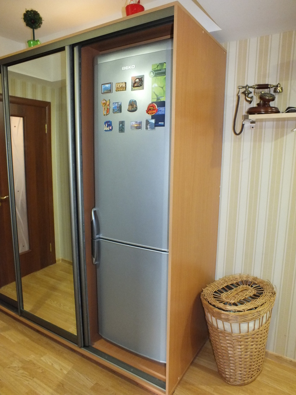 Высокий холодильник в шкафу купейного типа