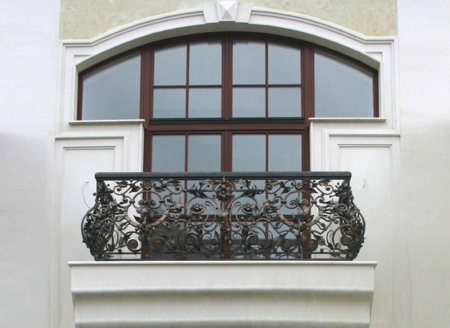Кованные перила на балконе дома с белыми стенами