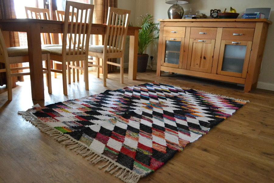 Пестрая окраска коврика на деревянном полу