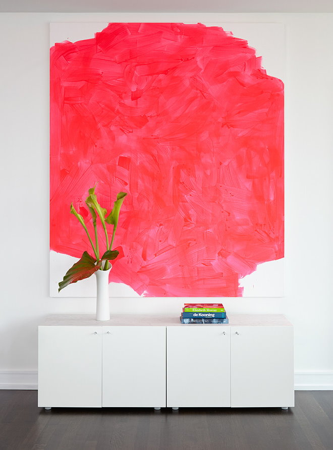 Красная абстракция на белой стене гостиной