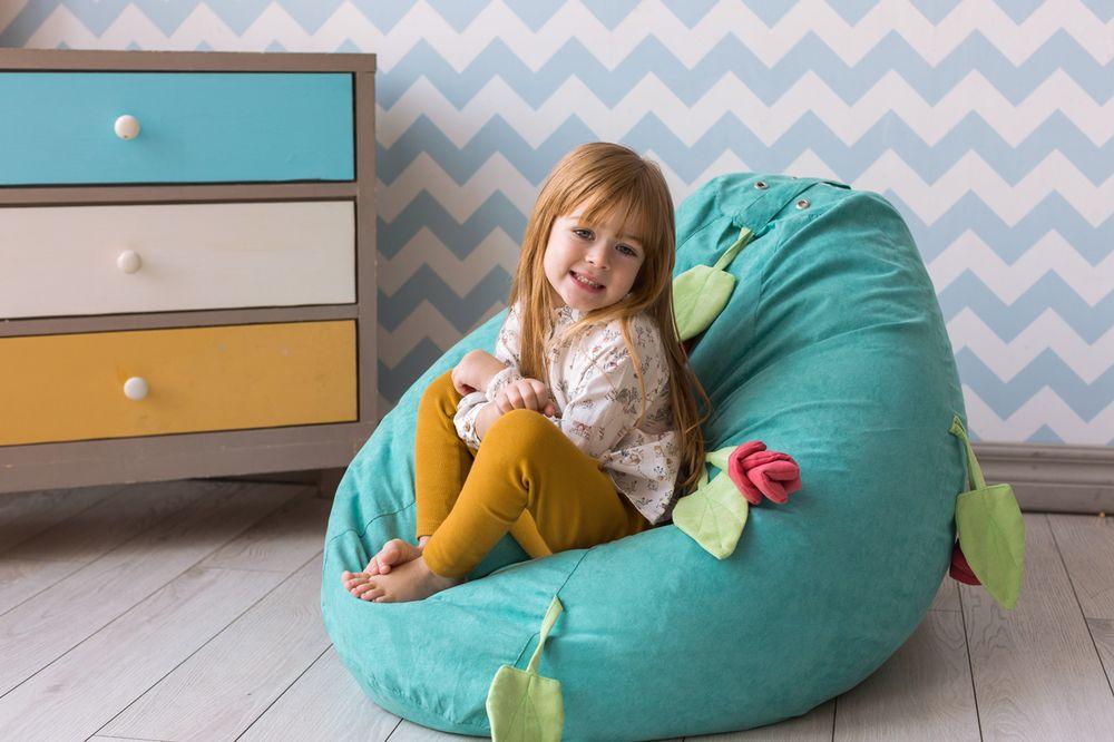 Маленькая девочка в мягком бескаркасном кресле