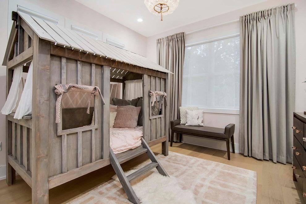 Деревянная кровать в виде домика в комнате ребенка
