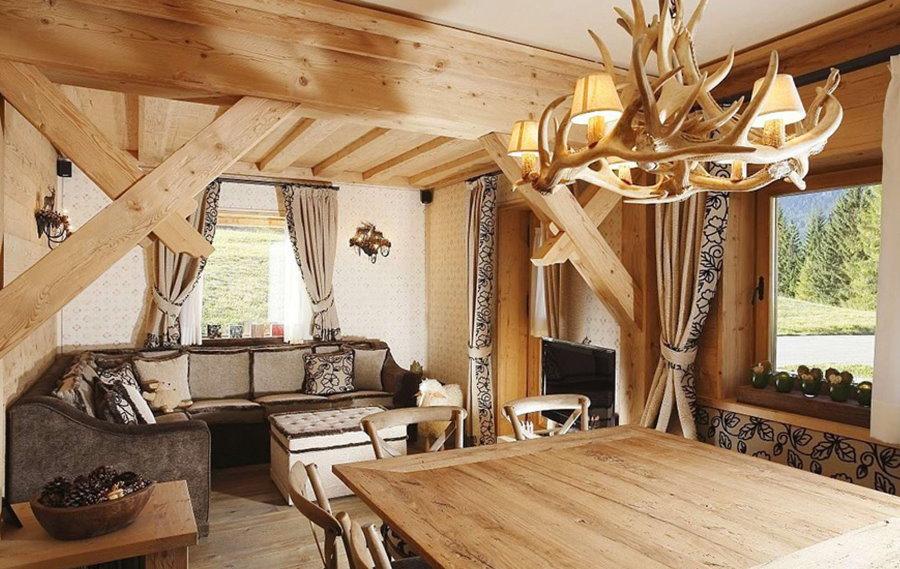 Люстра в виде рогов над деревянным столом