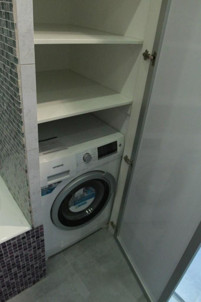Стиральная машина в нише стены ванной комнаты