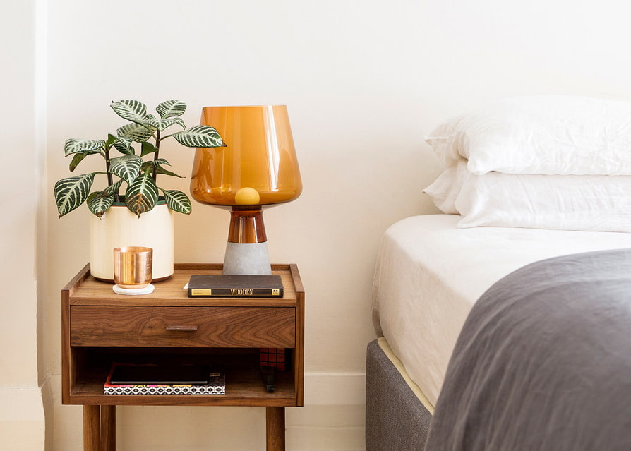 Комнатный цветок на тумбе возле кровати