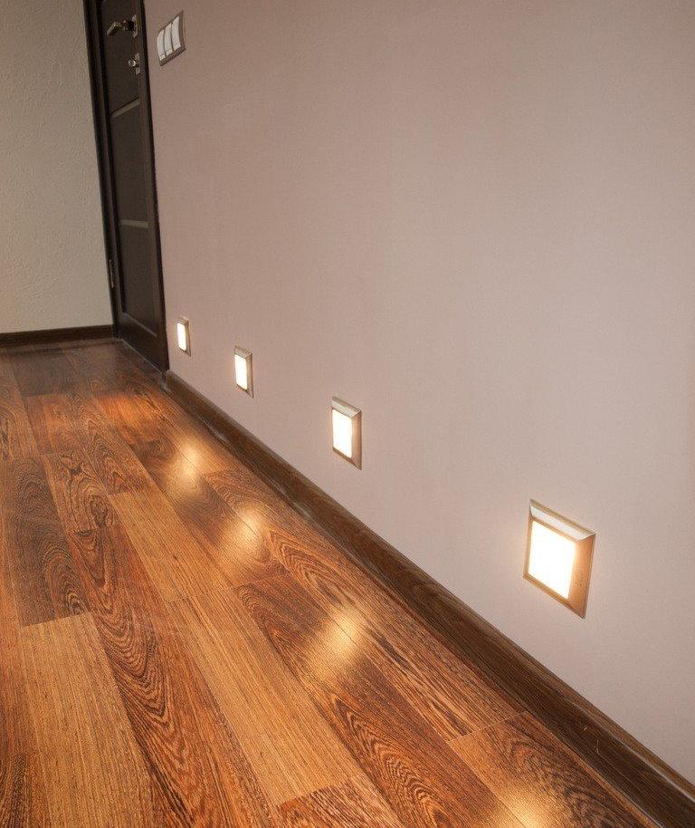 Квадратные светильники в нижней части стены коридора