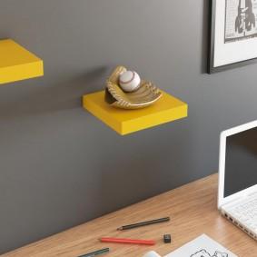 Небольшая желтая полочка на стене гостиной