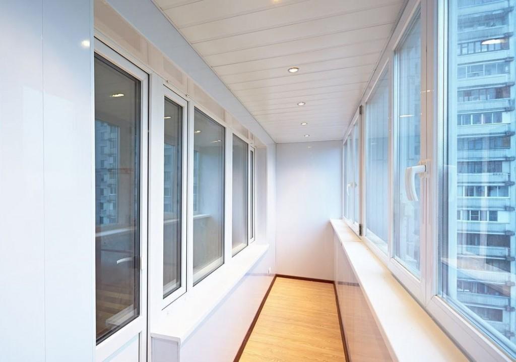 Интерьер длинной лоджии с панелями на потолке