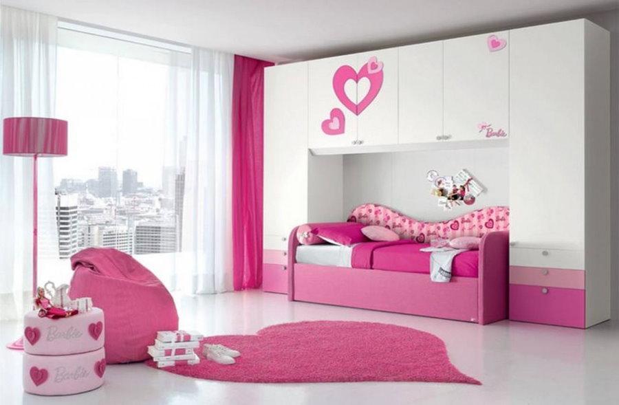 Розовая кровать в спальне девочки школьного возраста