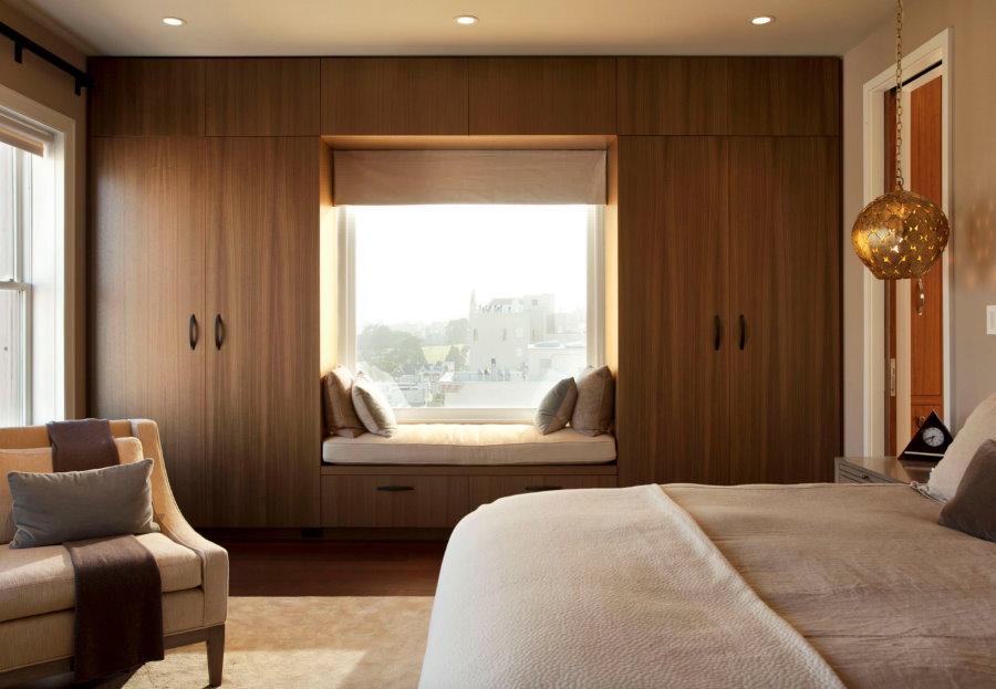 Встроенные шкафы вокруг окна в спальне девушки