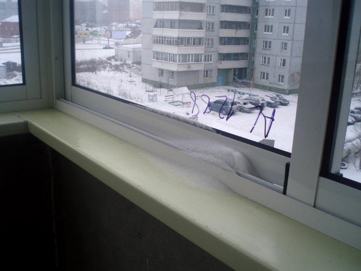 Снег на направляющей раздвижного окна на балконе