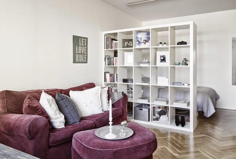 Белый стеллаж вместо перегородки в квартире студии