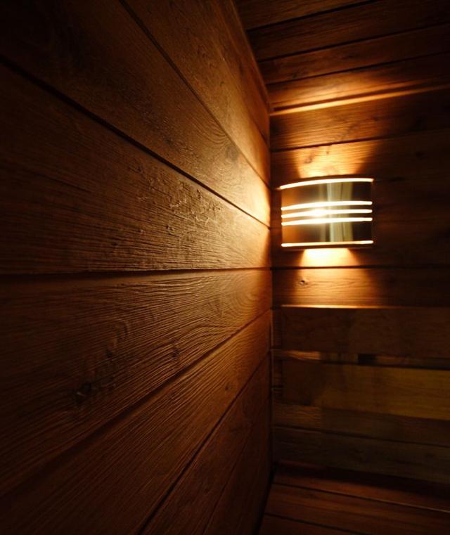 Специальный светильник на деревянной стене сауны