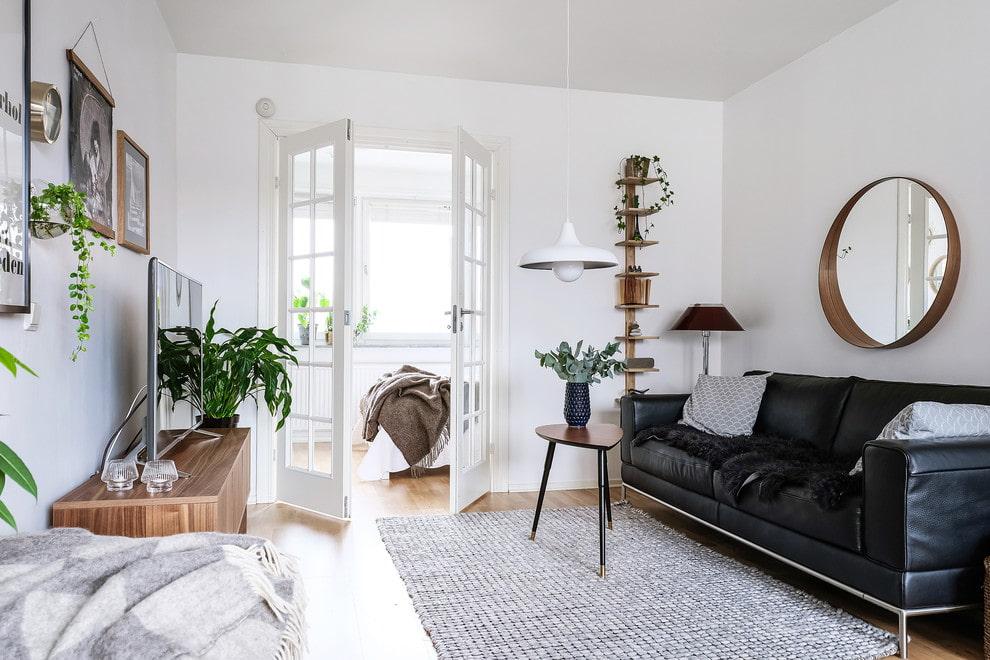 Черный диван в белой проходной гостиной