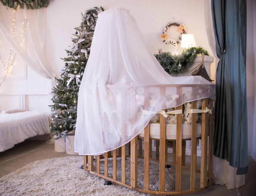 Тюлевый балдахин на деревянной кроватке для младенца