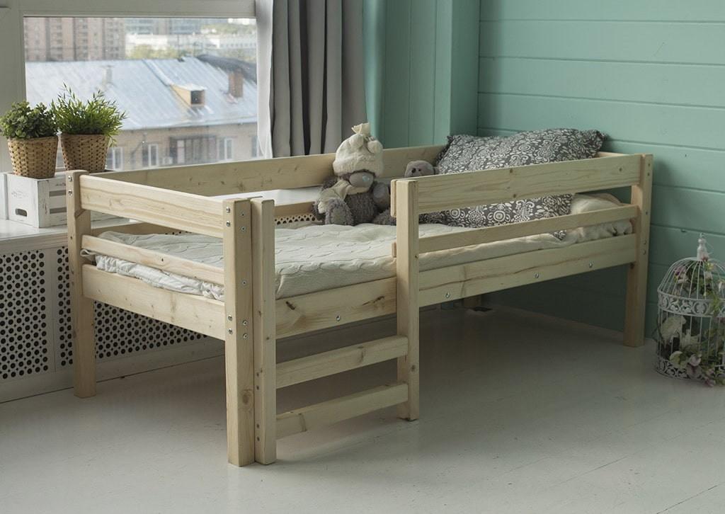 Детская кроватка из массива березы перед окном комнаты