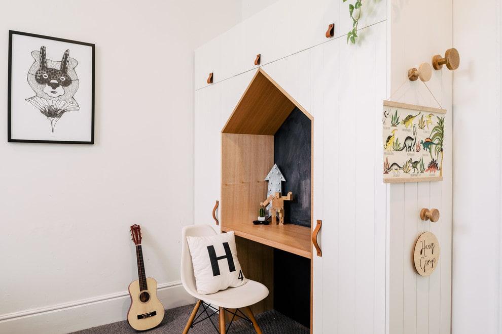 Детский стол между белыми шкафами