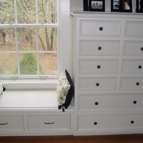 Белый комод у окна гостиной комнаты