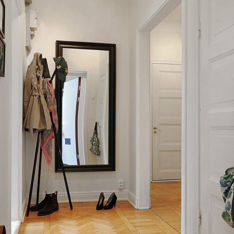Настенное зеркало в черной раме в белом коридоре