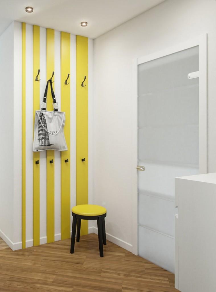 Желтая вешалка на белой стене прихожей