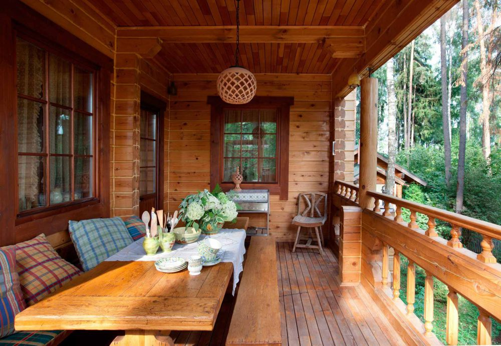 Обеденный стол на балконе деревенского дома