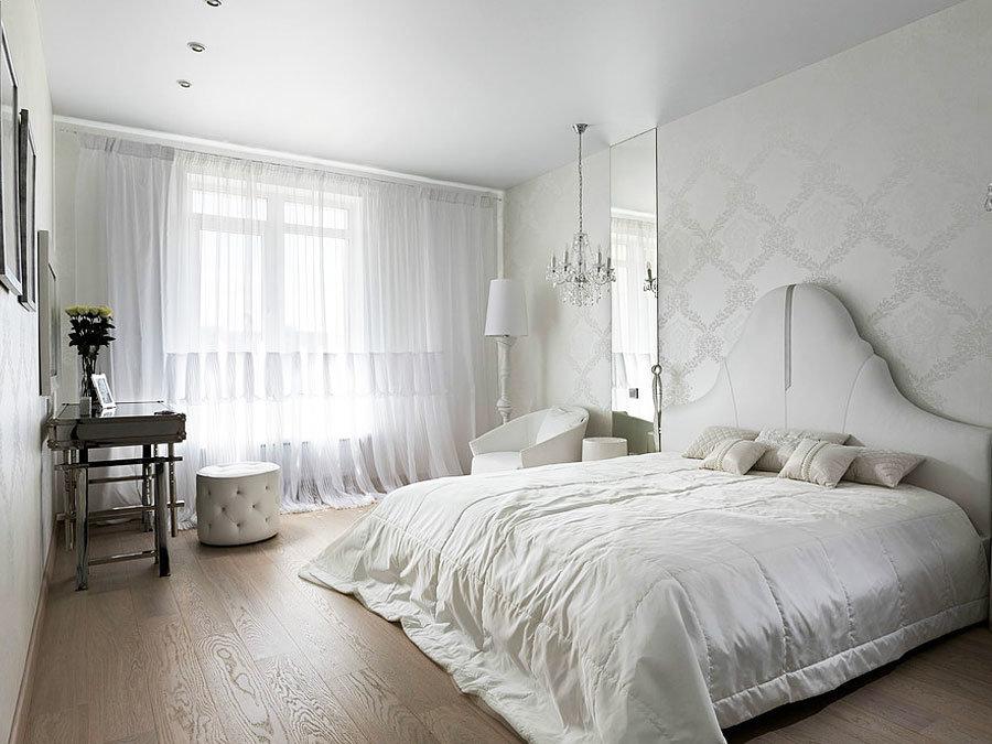 Белое одеяло на кровати в спальне