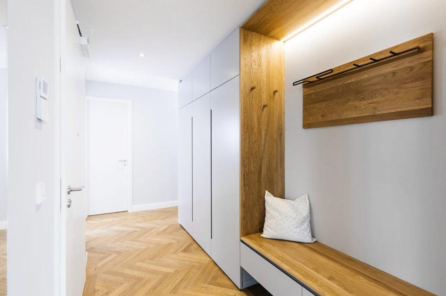 Деревянная вешалка на стене белого коридора
