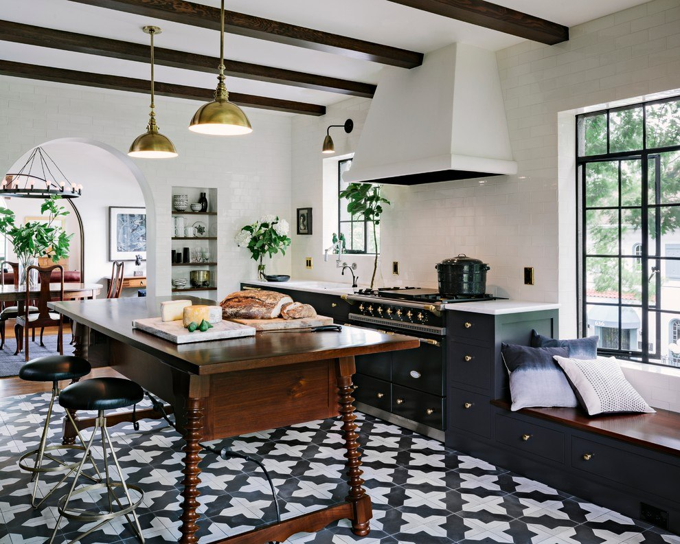 Деревянный стол в кухне-гостиной с черно-белой плиткой