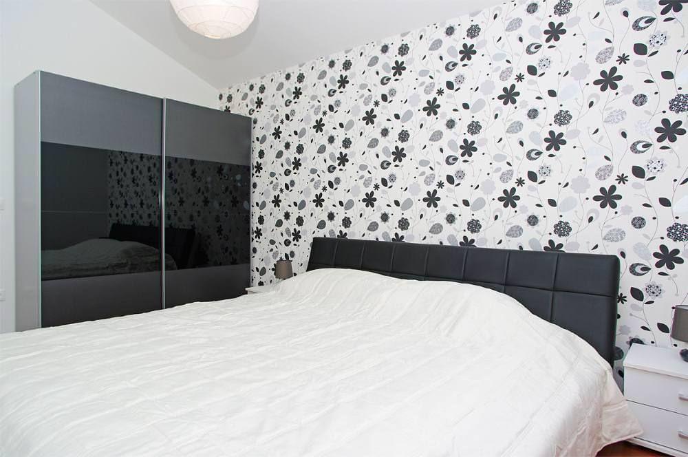 Черное изголовье кровати в спальне с бумажными обоями
