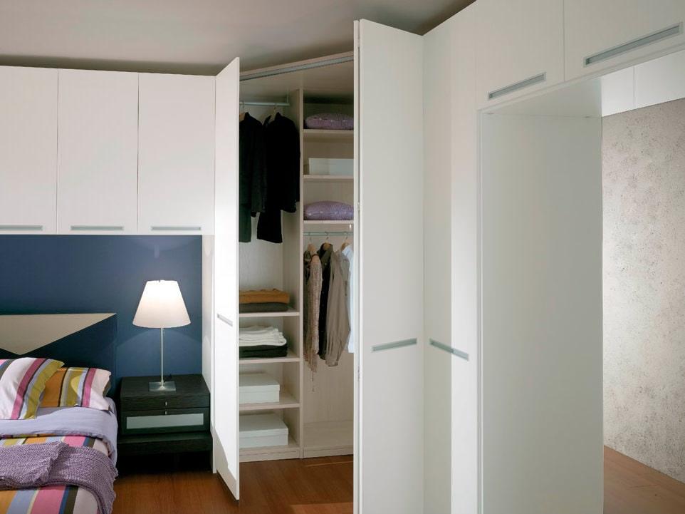 Диагональный шкаф в углу небольшой спальни