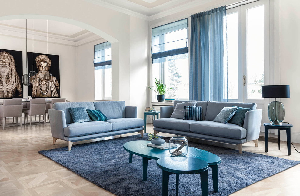 Два голубых дивана в гостиной с большими окнами