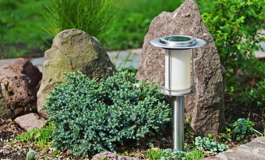 Компактный фонарик на клумбе в природными камнями