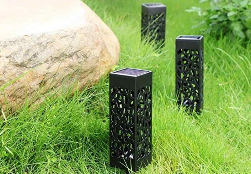 Солнечные светильники около каменного валуна
