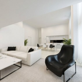 Черное кресло на белом полу гостиной