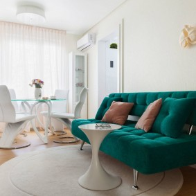 Изумрудный диван в интерьере комнаты