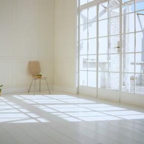 Большое окно в комнате с белыми стенами