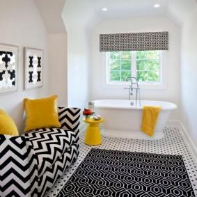 Желтое полотенце на бортике белой ванны