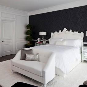 Белая кровать в спальне с черной стеной