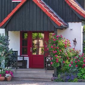 Цветы в вазонах перед деревянным крыльцом
