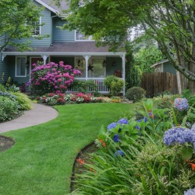 Ровный газон между цветочными клумбами