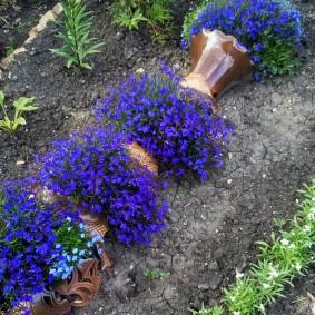 Клумба разбитая ваза с цветами синего оттенка