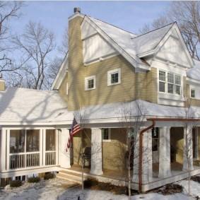 Снег на крыше загородного дома с двумя этажами