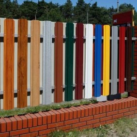 Разноцветная ограда из широкого штакетника