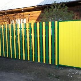 Желто-зеленый забор из оцинкованного штакетника