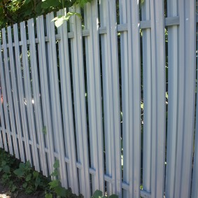 Простой забор из неокрашенного металлического штакетника