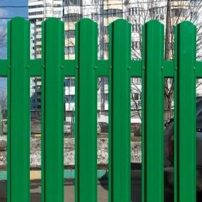 Зеленый забор с просветами между штакетинами