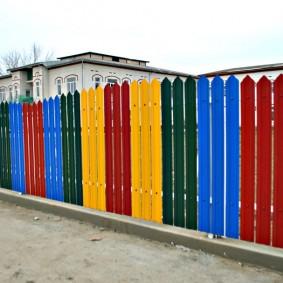 Разноцветная ограда на участке с жилым домом
